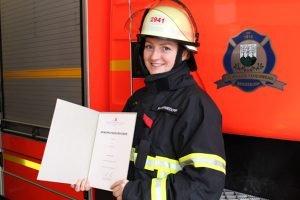 Feuerwehrfrau mit Beförderungsurkunde in vollständiger Persönlichen Schutzausrüstung vor einem Feuerwehrauto der Freiwilligen Feuerwehr Bergedorf