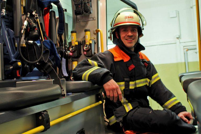Wehrführer Flo Hartart mit Schutzjacke und Helm der F2941 in der Halbnahen KAmeraeinstellung in einem Feuerwehrauto